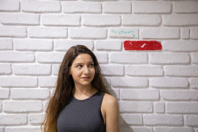 Aantrekkelijk vrouwelijk model die zich dichtbij een witte bakstenen muur met ??n enkele rode baksteen bevinden stock afbeelding