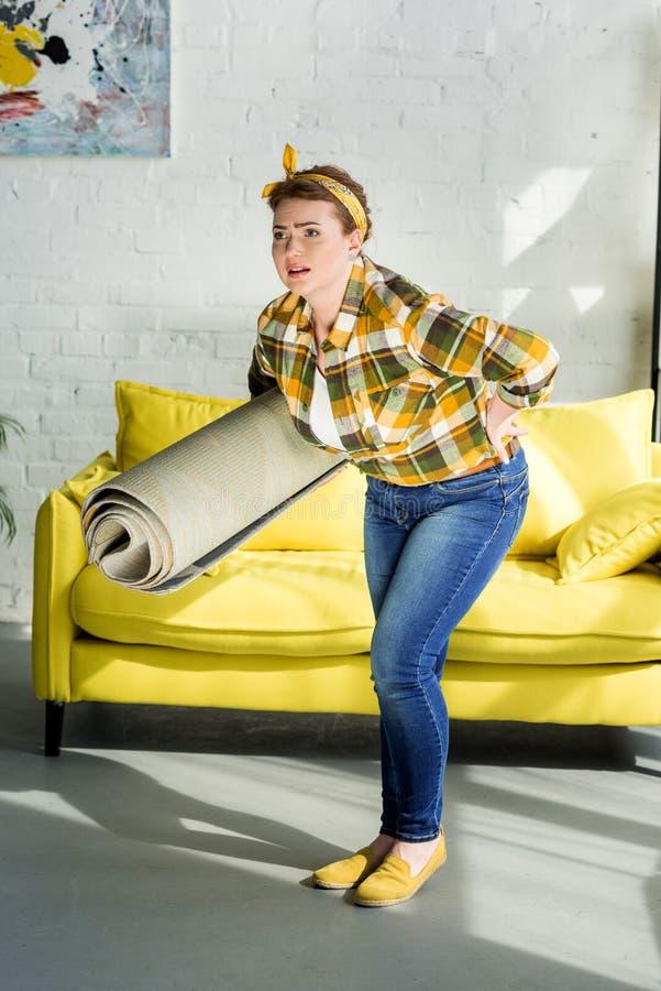 aantrekkelijk vrouwen dragend tapijt en het hebben van pijn in rug royalty-vrije stock fotografie