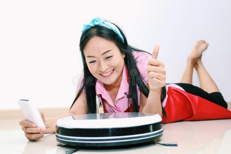 Aantrekkelijk vrouwengebruik van ver aan controle Slim schoon robotachtig vacuüm stock fotografie