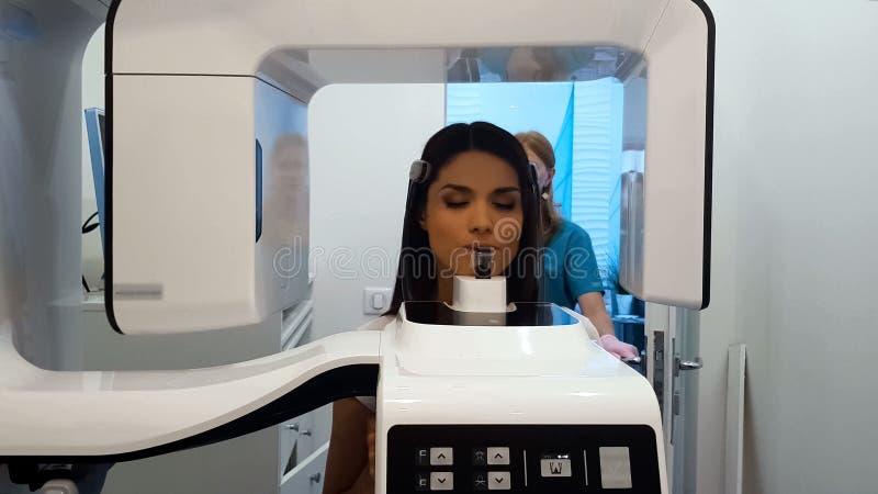 Aantrekkelijk wijfje die x-ray beeld van tanden in moderne de stomatologiekliniek maken stock fotografie