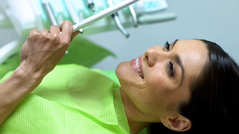 Aantrekkelijk wijfje die spiegel, resultaat bekijken van dichtingsproductplaatsing, tandheelkunde royalty-vrije stock fotografie