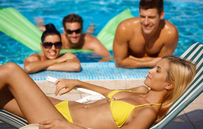 Aantrekkelijk wijfje en gezelschap door pool stock foto's