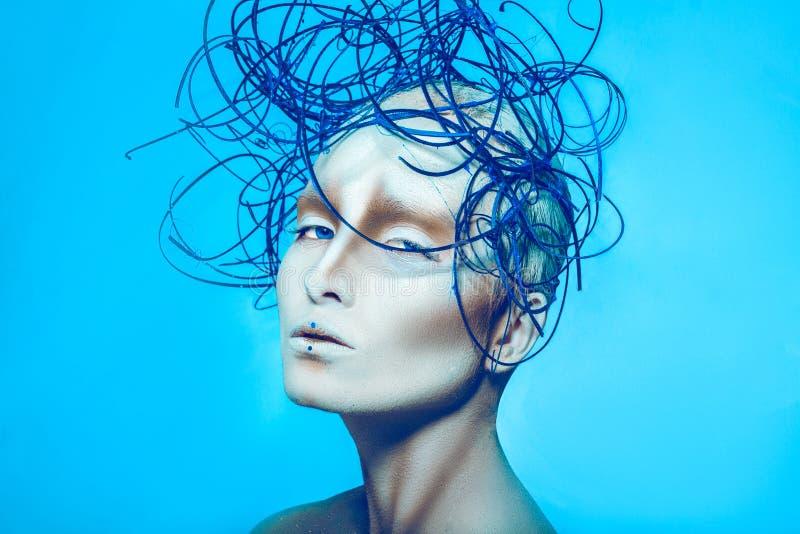 Aantrekkelijk wijfje met creatieve lichaamskunst en kapsel op blauwe B stock foto's