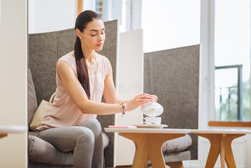 Aantrekkelijke aardige jonge vrouw die heerlijke thee drinken royalty-vrije stock foto