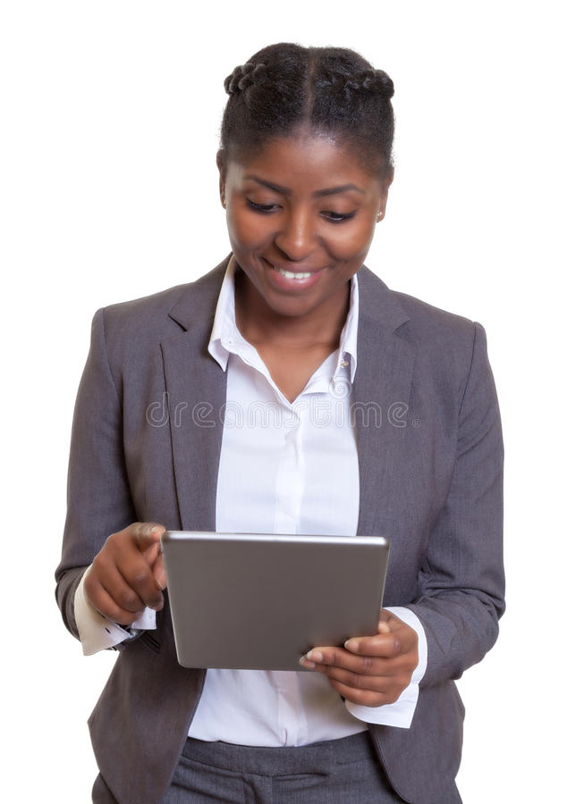 Aantrekkelijke Afrikaanse onderneemster die met tabletcomputer werken stock afbeelding