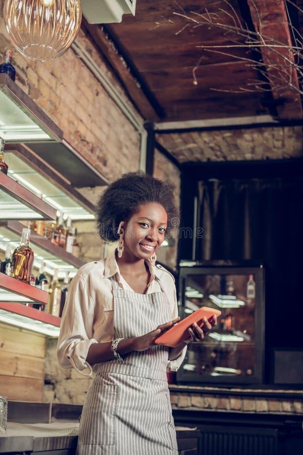 Aantrekkelijke Afro-Amerikaanse barista die van de zolderbar ordeinformatie toevoegen aan basis royalty-vrije stock afbeelding