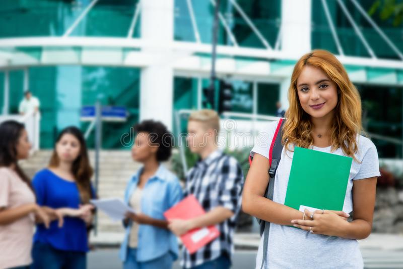 Aantrekkelijke Amerikaanse vrouwelijke student met groep internationaal p stock afbeelding