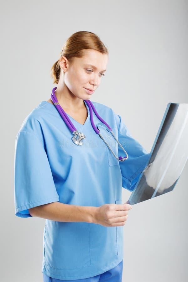 Aantrekkelijke arts of radioloog die onderzoekend een x-ray film in het ziekenhuis bevinden zich aangezien zij op vooruitgang con stock afbeelding