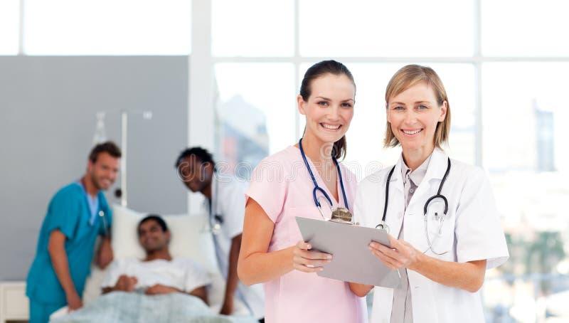 Aantrekkelijke artsen die bij een patiënt aanwezig zijn royalty-vrije stock foto's