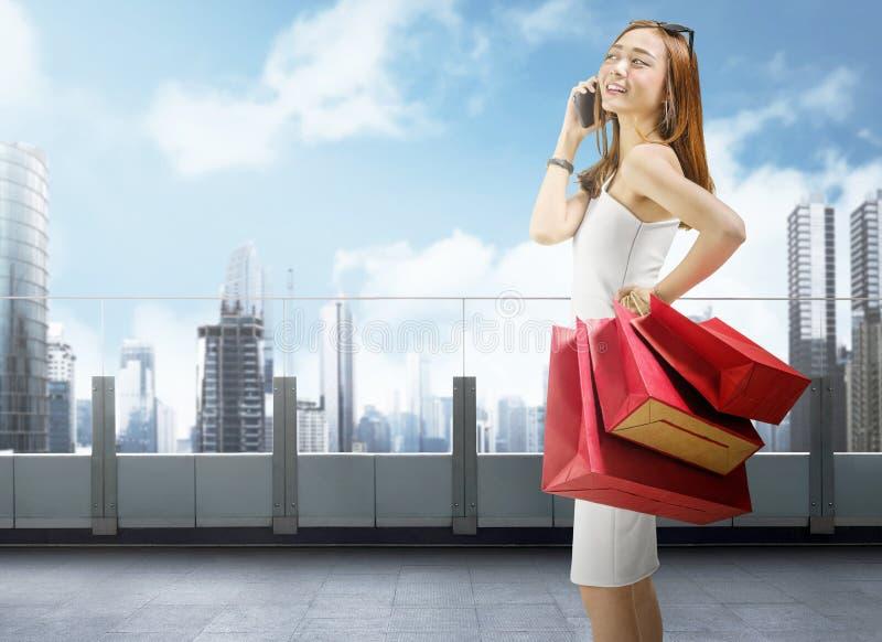 Aantrekkelijke Aziatische vrouw die mobiele telefoon met behulp van terwijl het dragen van het winkelen royalty-vrije stock afbeelding