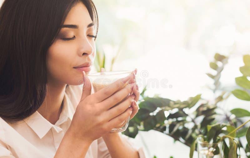 Aantrekkelijke Aziatische vrouw die van de geur van ochtendkoffie genieten royalty-vrije stock foto