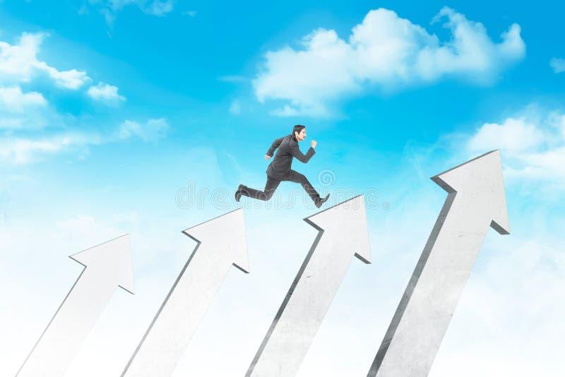 Aantrekkelijke Aziatische zakenman die boven witte pijlen springen stock afbeelding