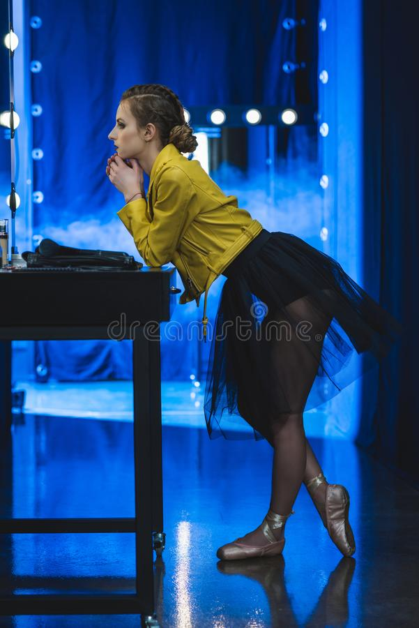 aantrekkelijke ballerina die in tutu en geel leerjasje in spiegel met gloeilampen kijken royalty-vrije stock afbeelding