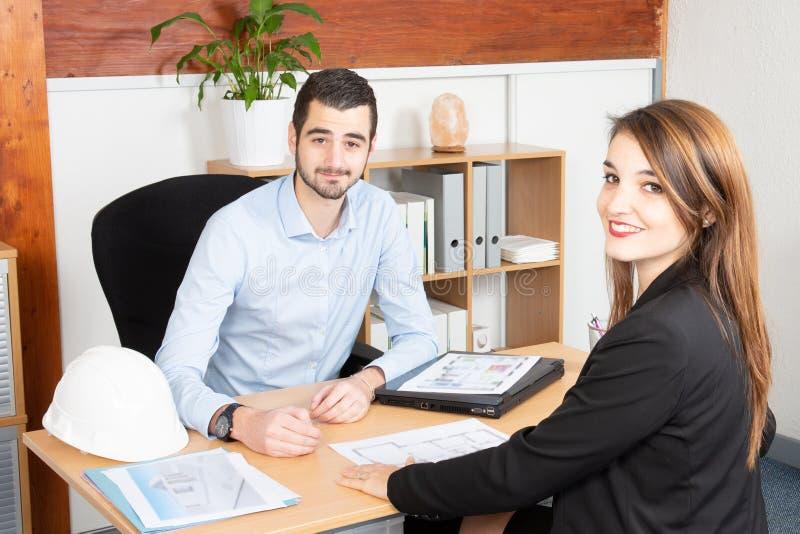 Aantrekkelijke bedrijfsmensen die in de de bureauman en vrouw werken in commerciële vergadering royalty-vrije stock afbeeldingen