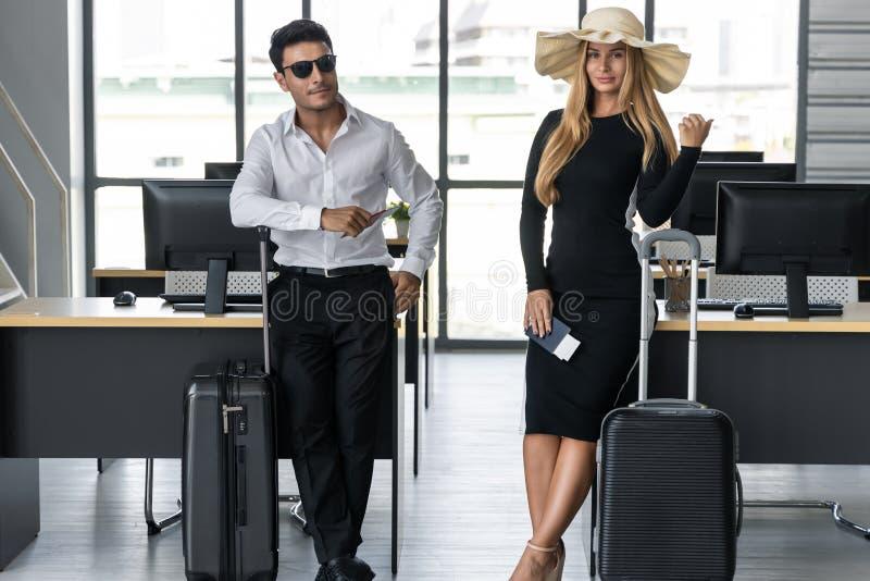 Aantrekkelijke bedrijfsmensen die paspoort en bagage in werkplaats van bureau houden Het concept van de zomervakanties royalty-vrije stock foto's