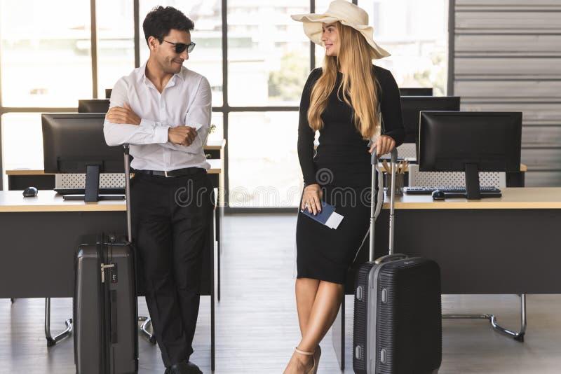 Aantrekkelijke bedrijfsmensen die paspoort en bagage in werkplaats van bureau houden Het concept van de zomervakanties royalty-vrije stock afbeeldingen