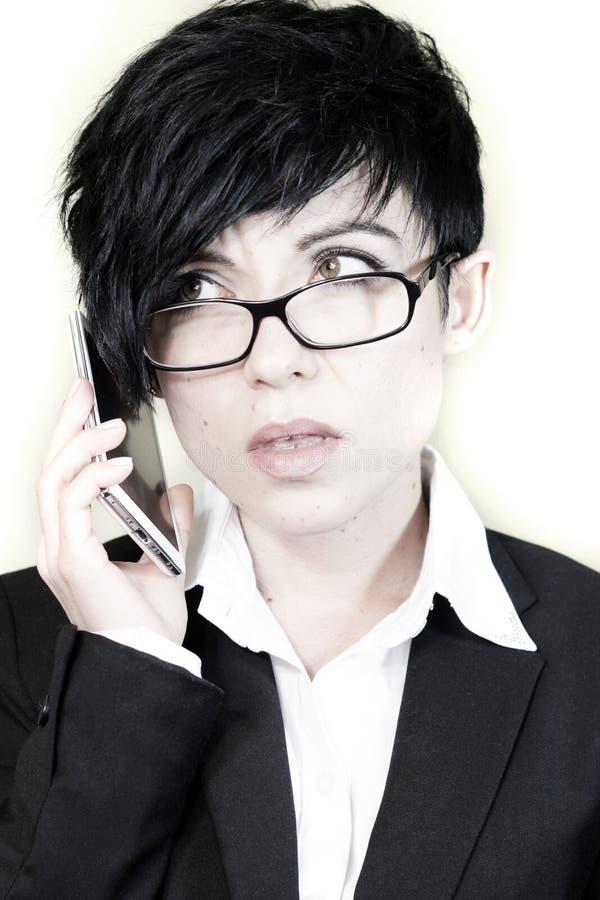 Aantrekkelijke bedrijfsvrouw die bij smartphone spreken stock afbeeldingen