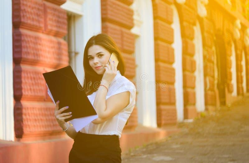 Aantrekkelijke bedrijfsvrouw die op de telefoon spreken en de camera bekijken het het werk proces stock fotografie