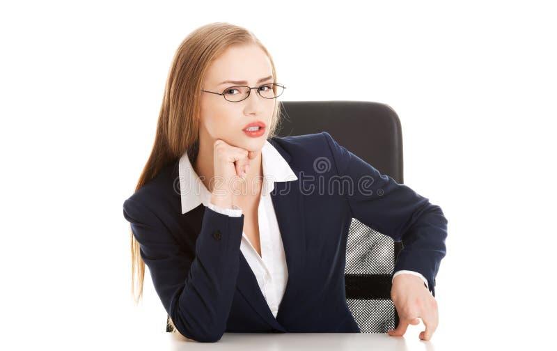 Aantrekkelijke bedrijfsvrouw door de lijst, bazig gedrag. stock foto