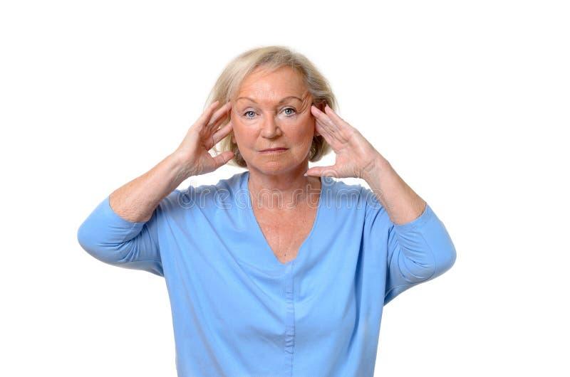 Aantrekkelijke bejaarde dame die aan een hoofdpijn lijden royalty-vrije stock foto's