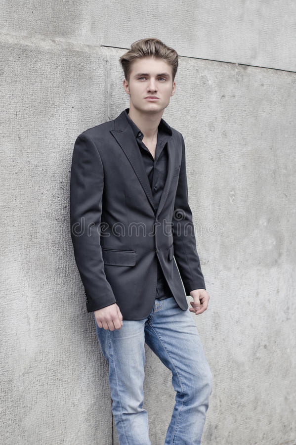 Aantrekkelijke blauwe eyed, blonde jonge mens die tegen witte muur leunen royalty-vrije stock foto's