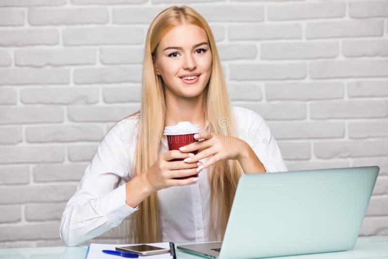 Aantrekkelijke blonde bedrijfsvrouw die aan haar laptop en het drinken koffie in haar bureau werken royalty-vrije stock fotografie