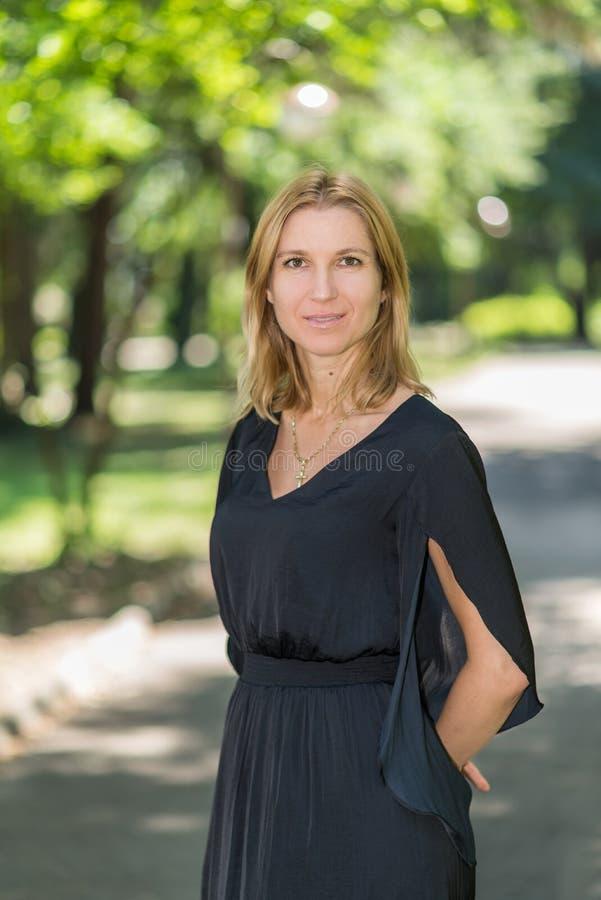 Aantrekkelijke blonde jonge vrouw in een park royalty-vrije stock afbeelding