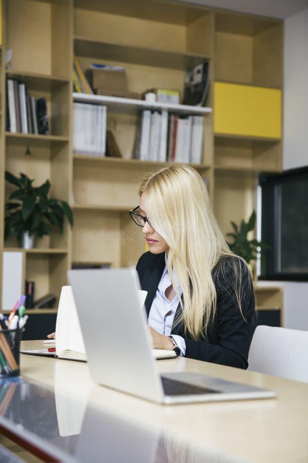 Aantrekkelijke blonde onderneemster die in modern bureau werken stock afbeeldingen
