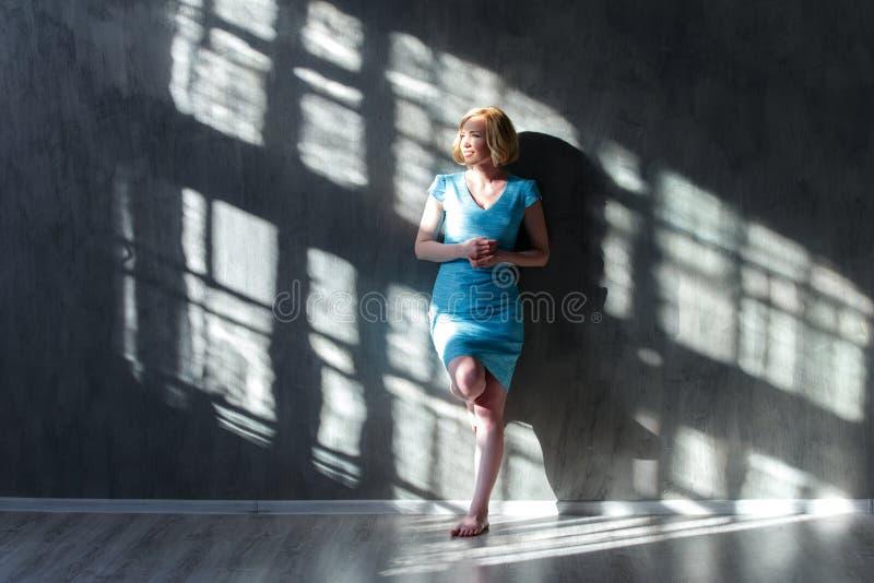 Aantrekkelijke blonde vrouw die op de muur en het loensen leunen stock afbeelding