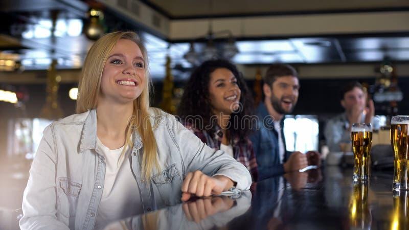 Aantrekkelijke blonde vrouw die van tijd met vrienden die in bar genieten, sporten op gebeurtenis letten stock fotografie