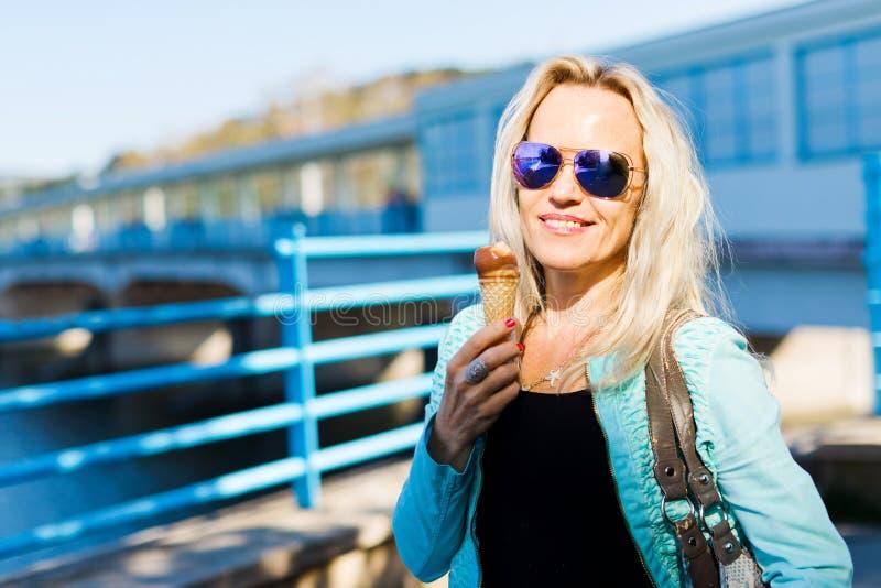 Aantrekkelijke blonde vrouw die in zonglazen de stad in - roomijs lopen royalty-vrije stock foto's