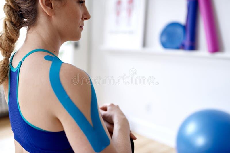 Aantrekkelijke blonde vrouw in een helder bureau van de sporttherapie met kinesioband op haar hals en schouder om pijn te helen stock afbeelding