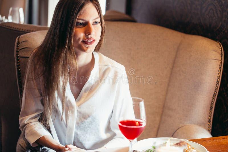 Aantrekkelijke blonde vrouw het drinken wijn in luxebinnenland stock afbeeldingen