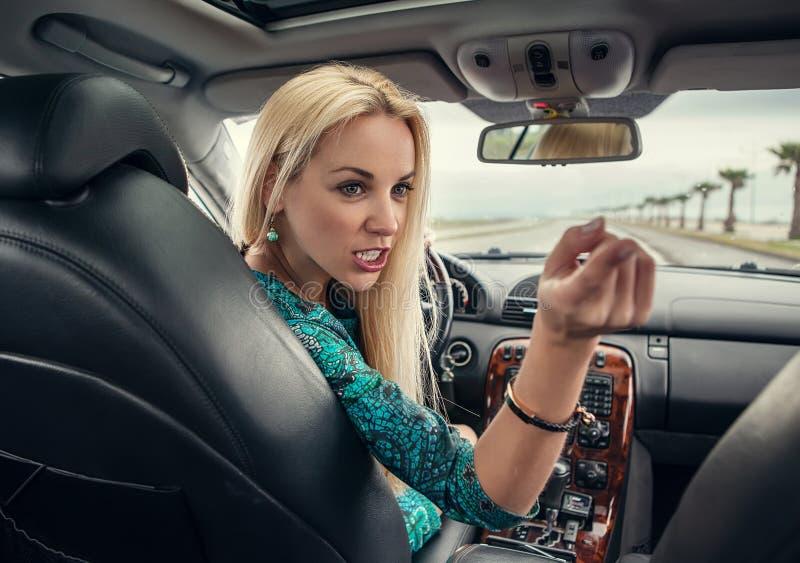 Aantrekkelijke blonde vrouwelijke emotionele besprekingen aan achterzetelpassagier stock afbeelding