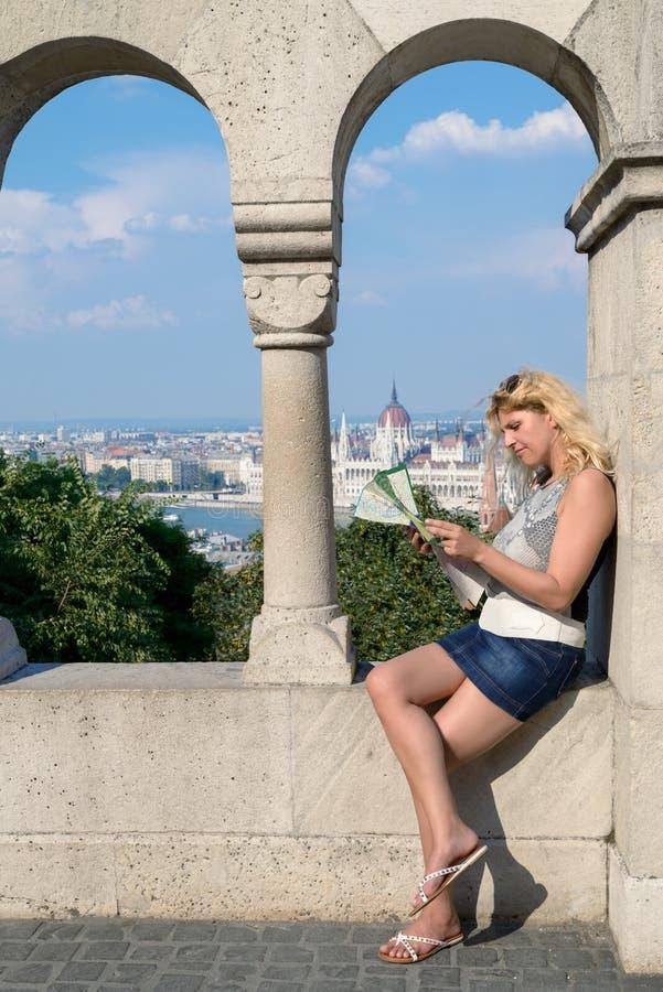 Aantrekkelijke blonde vrouwelijke reiziger met toeristenkaart in centrall stock foto