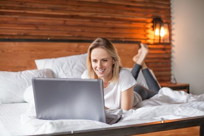 Aantrekkelijke blondevrouw die notitieboekjecomputer met behulp van terwijl het liggen in bed stock afbeelding
