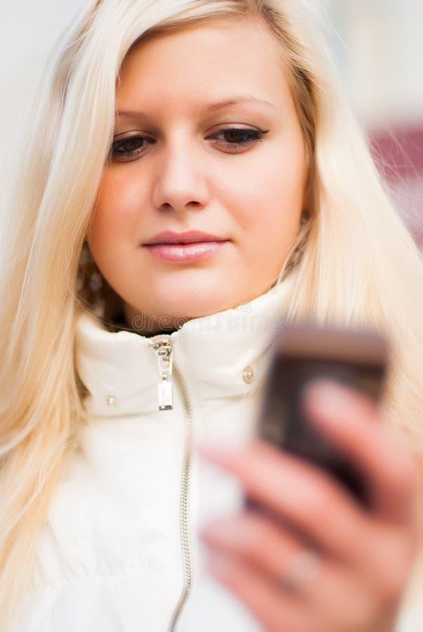 Aantrekkelijke blondevrouw met mobiele telefoon royalty-vrije stock afbeelding