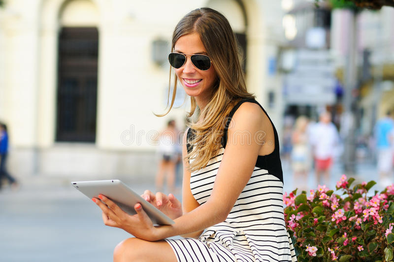 Aantrekkelijke blondevrouw met tabletcomputer op stedelijke achtergrond royalty-vrije stock afbeelding