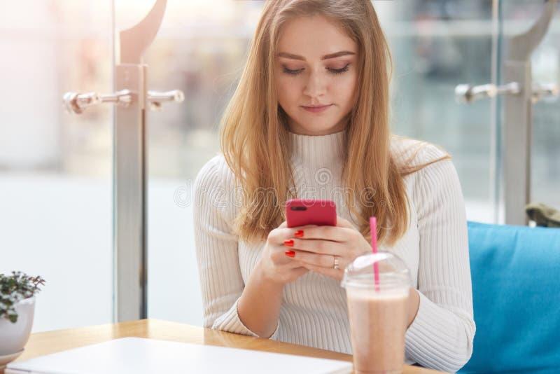 Aantrekkelijke blondevrouw in witte overhemdszitting bij koffie op blauwe bank, holdings mobiele telefoon, die met haar vrienden  stock afbeelding