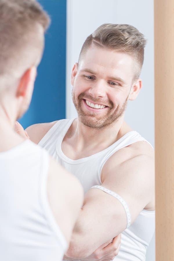 Aantrekkelijke bodybuilder die zijn bicepsen meten stock foto's