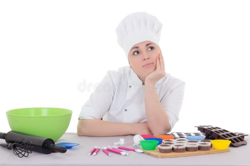 Aantrekkelijke bored vrouwelijke banketbakker in kok eenvormige zitting bij royalty-vrije stock foto's