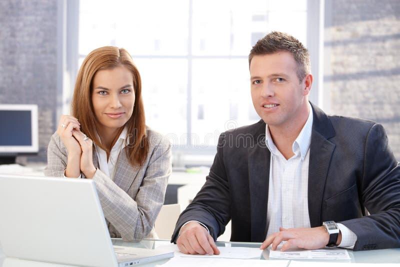 Aantrekkelijke businesspeople die aan laptop werken stock afbeelding