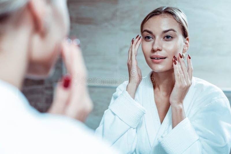 Aantrekkelijke dame die met rode spijkers gezichtsroom toepassen stock fotografie