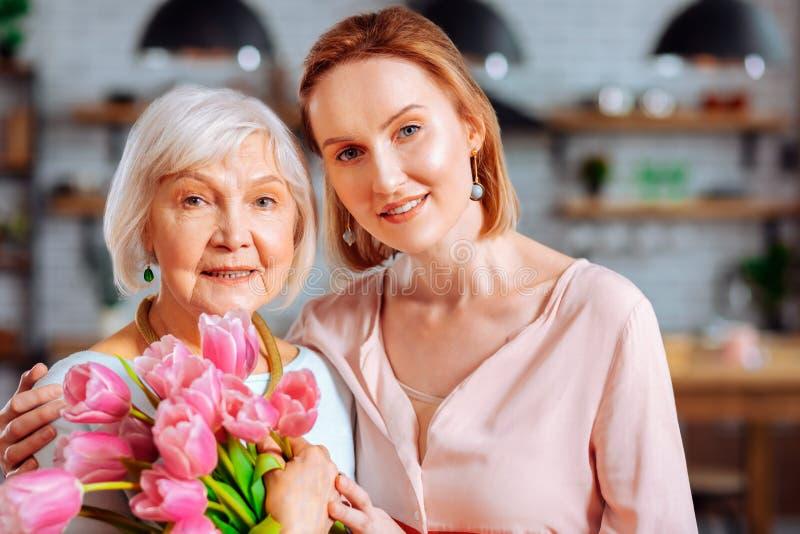 Aantrekkelijke dame die verouderd mamma met bos van tulpen knuffelen stock foto