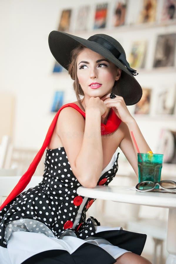 Aantrekkelijke dame met zwarte hoed en rode sjaalzitting in restaurant stock afbeelding