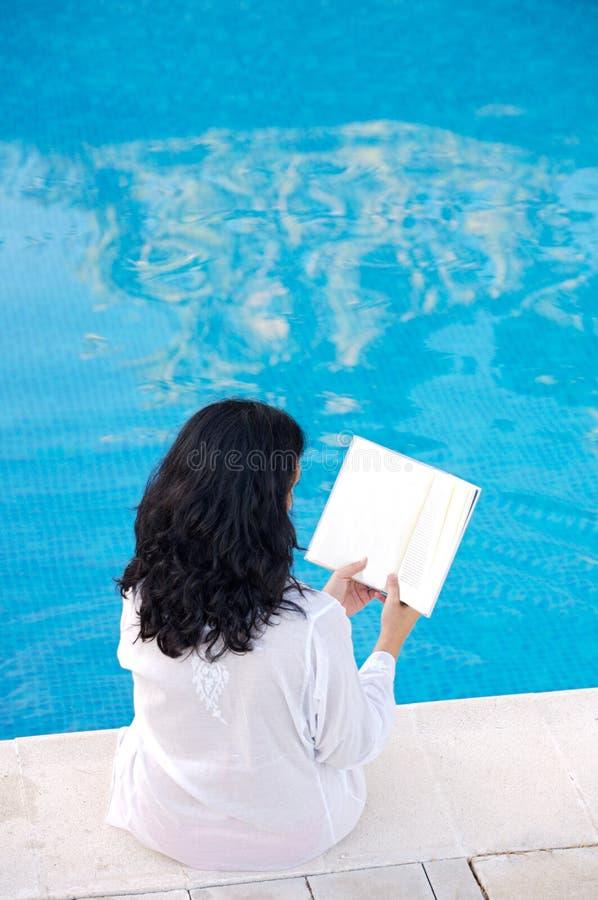 Aantrekkelijke damelezing in het zwembad royalty-vrije stock afbeelding