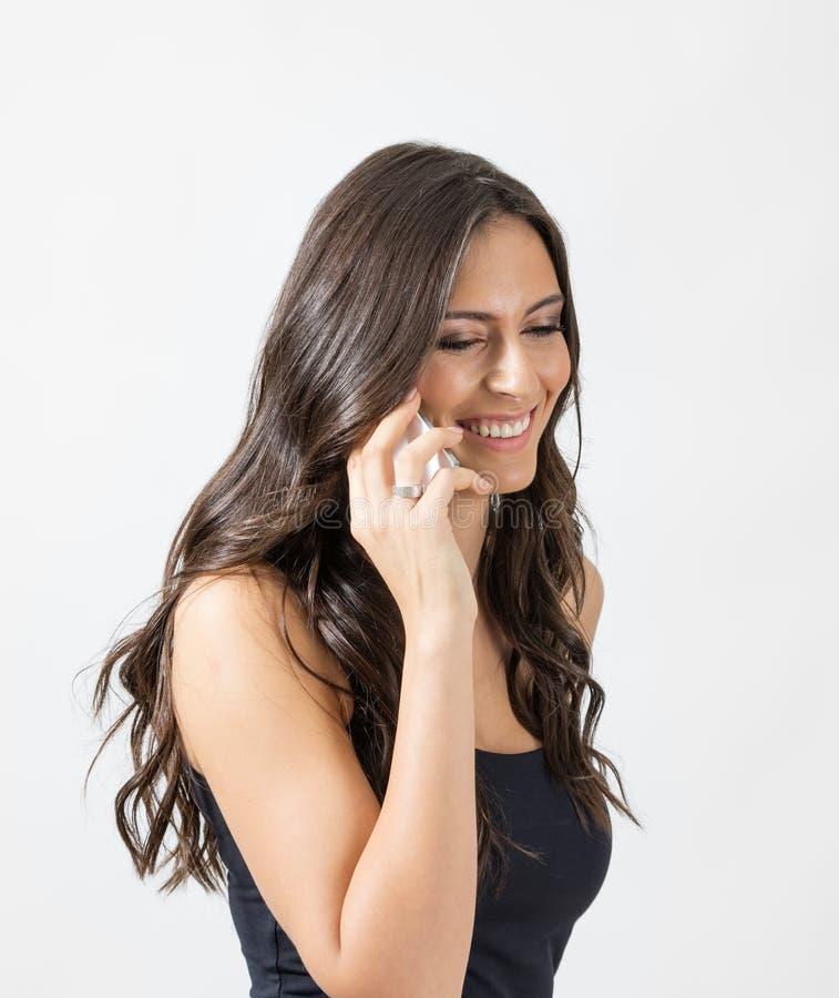 Aantrekkelijke donkerbruine schoonheid die spontaan terwijl het spreken op de mobiele telefoon lachen royalty-vrije stock afbeelding