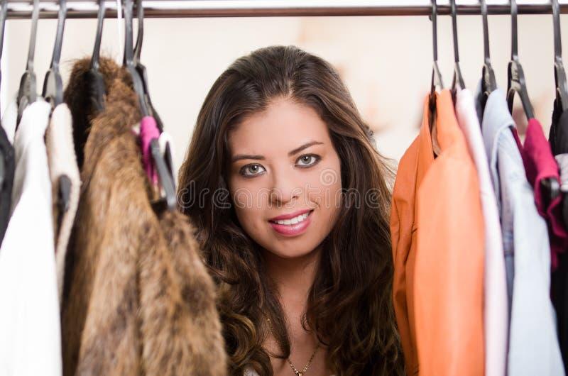 Aantrekkelijke donkerbruine status met hoofd binnen - tussen kleren bij kledingsrek, het winkelen manierconcept stock foto's