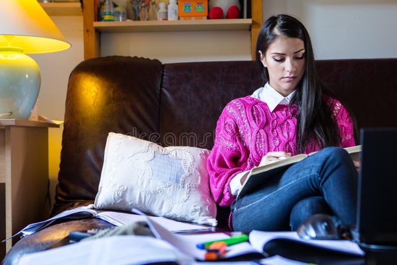 Aantrekkelijke donkerbruine studentelezing die in haar girly ruimte bestuderen stock foto's