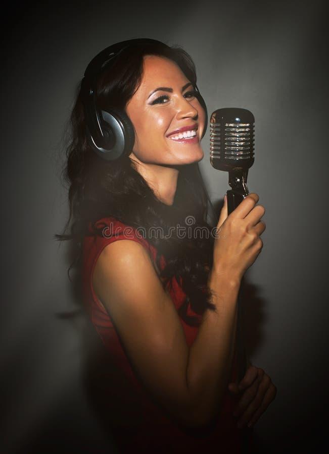 Aantrekkelijke donkerbruine vrouw die een lied registreren stock foto's